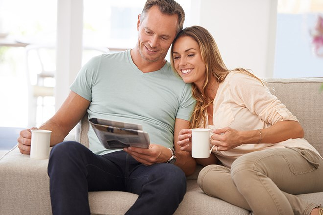 Man and woman sitting on the couch drinking coffee together