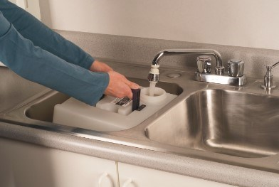Person filling BISSELL® Big Green® Tank with water from sink